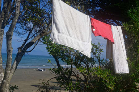 Towels and a red t-shirt are hanging on a line to dry at a sea side campground
