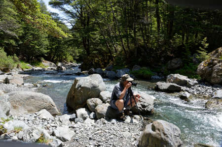 A photographer crouches behind his tripod, taking a photo of a river