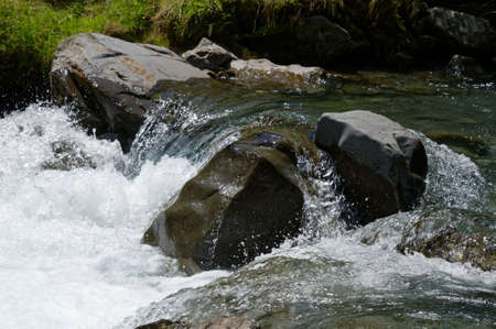 Water runs over the top of a boulder into frothy white water below