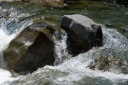 Fast water runs over and around a large boulder in a river