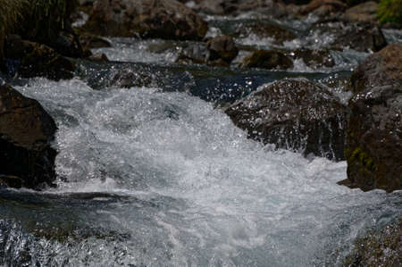 A river bed has frothy, white water from the flow of the water 版權商用圖片