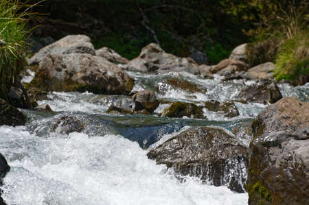 The force of the water creates white water in between boulders in a river Stock fotó