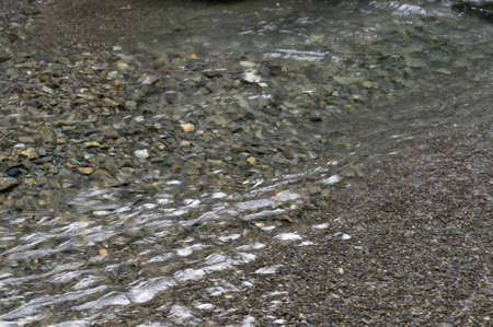 Grey stones form the bed of a shallow river