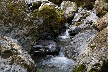 A river cascades down over rocks, between boulders,