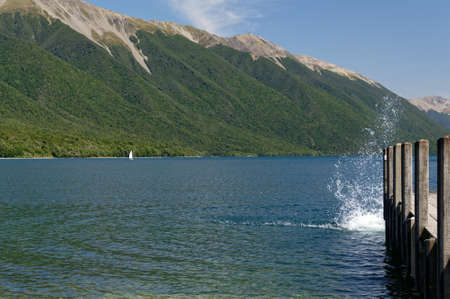 Mountains surround Lake Rotoitit as a swimmer enjoys a refreshing dip by jumping off the wharf