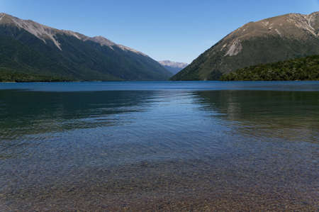 The clear waters of Lake Rotoiti move from the shallows out to the deep blue green water of the Lake, with the mountains behind