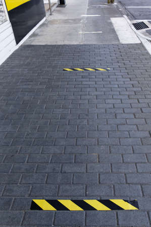 Social distancing, yellow and black strips on the pavement in Motueka showing where to stand to maintain safe distanes from the person in front in the queue