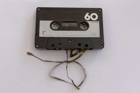 Broken tape spills out the bottom of an analogue cassette tape