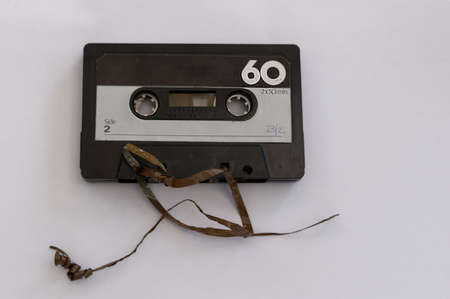 An analog magnetic tape cassette has had its tape unravelled
