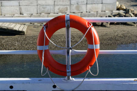 A safety precaution, an orange life ring is roped to rails on a pier by the sea