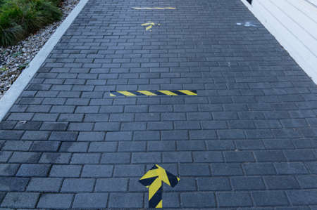 Social distancing lines and arrows are stuck to the pavement outside a shop to remind people about social distancing 版權商用圖片 - 150018751