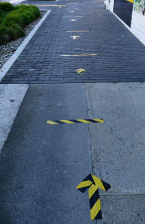 Yellow and black tape on the pavement to show where to stand to maintain safe distances from the person in front of you in the queue to enter a business. Social distancing is implemented to prevent the spread of the virus.