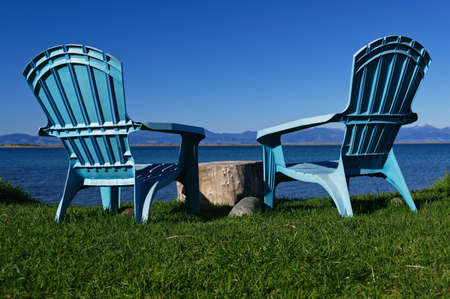 Two blue chairs are on grass looking out to the sea views and the mountains beyond. A tree stump is used as a table 版權商用圖片 - 150359051
