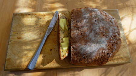 Home made bread sits on the bread board, a slice has been buttered ready to eat 版權商用圖片