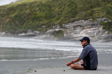 A man is sitting in the lotus position looking out to sea 版權商用圖片