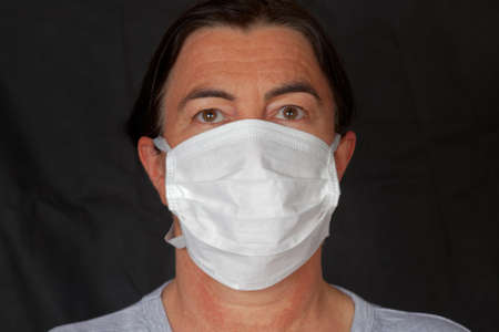 A face mask is worn to prevent the spread of disease.  The wearing has been implemented during pandemic 版權商用圖片