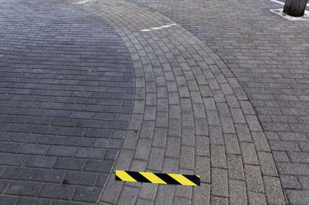 Yellow and black lines on the pavement mark the safe distance to stand to ensure social distancing requirements are met during the Covid 10 coronavirus out break