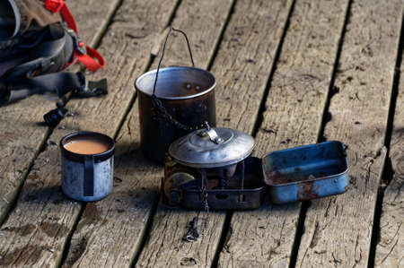 A tin mug of milky tea sits with a billy and other pots 版權商用圖片