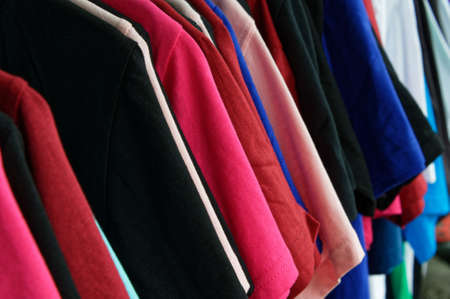 Different coloured shirts hang in a row