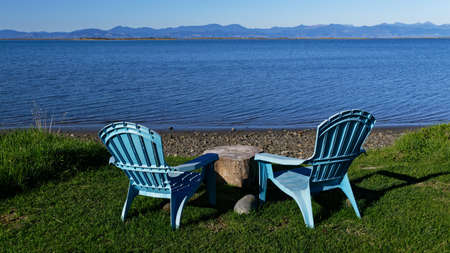 A pair of blue plastic chairs sit by the sea side.  They have a tree trunk for a table.  A great place for a picnic.