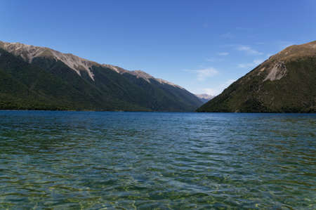 The clear waters of Lake Rotoiti invite you in for a swim, they are surrounded by mountains.