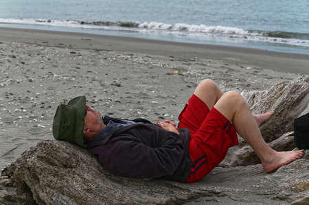 Simple pleasures, a man is lying on a log on the beach