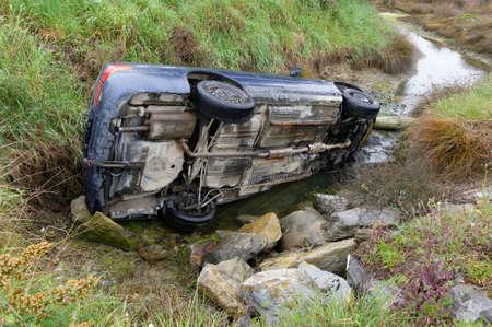 A car crash risks environmental damage as oil and petrol enter a natural waterway