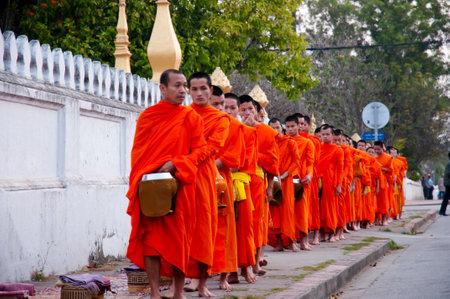 limosna: Luang Prabang, Laos - 16 de febrero de 2011: el ritual diario de los monjes recoger limosnas y ofrendas Editorial