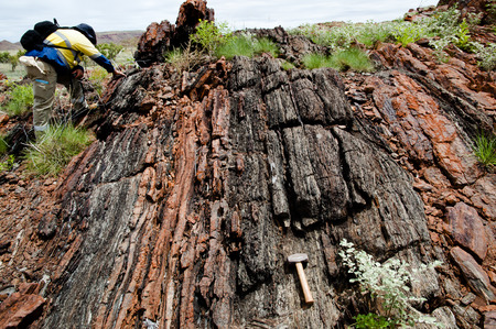Geologist Examining a Banded Iron Formation- Pilbara - Australia Stock Photo - 55643994