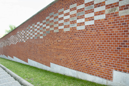 contributed: KRAKOW, POLAND - July 7, 2016: The contribution wall was built by the Austrians with plaques bearing the names of institutions and citizens who contributed to the revival of Wawel after 1918 Editorial