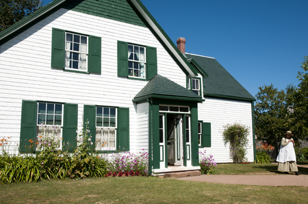 house gables: CAVENDISH, CANADA - August 9, 2016: Anne of Green Gables impersonator beside her house on Prince Edward Island