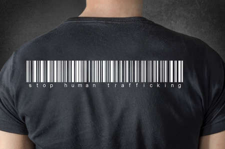 female prisoner: Stop human trafficking tittle and barcode on black t-shirt. Back view.