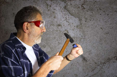 gad: Construction worker wears safety glasses and holds hammer and gad tool.