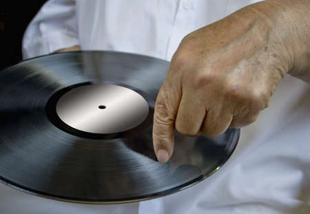 making music: Person holding vinyl record pointing to the plate. Concept of making music.