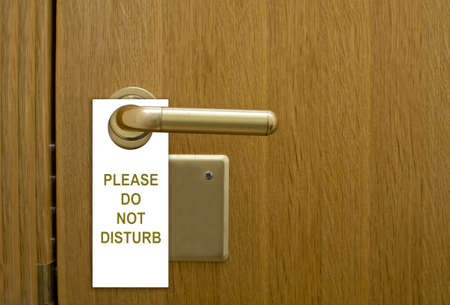 common room: Please do not disturb message, a common request for others not to disturb the motel or resort room occupants, on a paper cardboard tag hung on the door knob of a hotel
