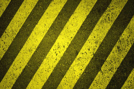 Black and yellow hazard lines on asphalt background
