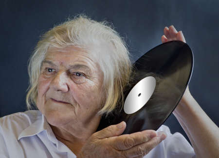 remembering: An elderly woman listening LPs. Remembering the past.