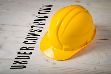 website words: Under Construction stencil print on wooden background with safety helmet. Stock Photo