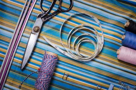 Sewing accessories - thread, scissors, needles, buttons, ribbons on the fabric. Tailoring concept. Stock Photo