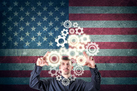 Businessman touching gear elements with US flag background. Corporate business concept.