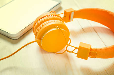 Orange headphones and tablet on wooden table