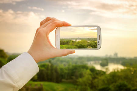 Travel concept - tourist takes a picture of beautiful city panorama in summer on smartphone
