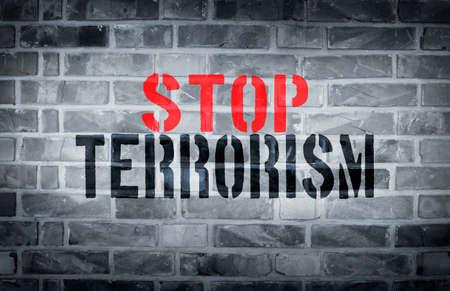 dangerous ideas: Stop Terrorism stencil print on the grunge white brick wall