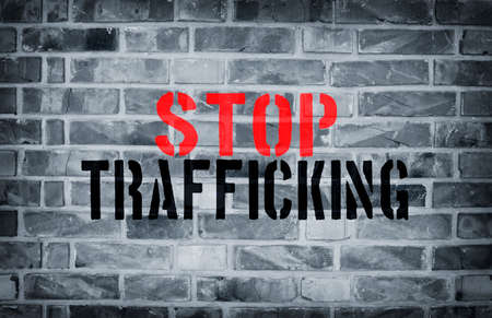 Stop Human Trafficking stencil print on the grunge white brick wall Stock Photo - 80635238