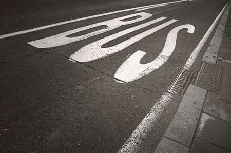 Bus stop sign painted on asphalt road