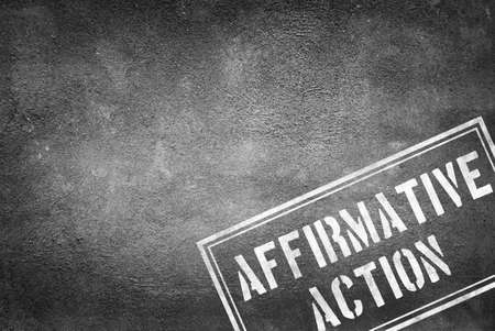 Affirmative action stamp on concrete wall Stock Photo