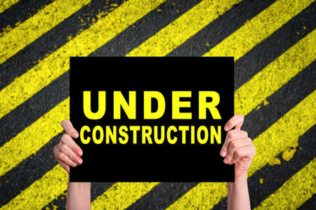 Under Construction card with safety stripes on construction site. Stock Photo