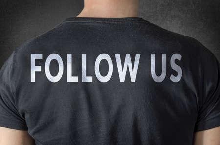 back link: FOLLOW US tittle on black t-shirt. Back view.