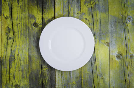 vintage dishware: Empty white plate on wooden table
