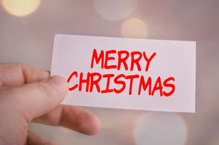 Card in hand with the word Merry Christmas on bokeh background Stock Photo